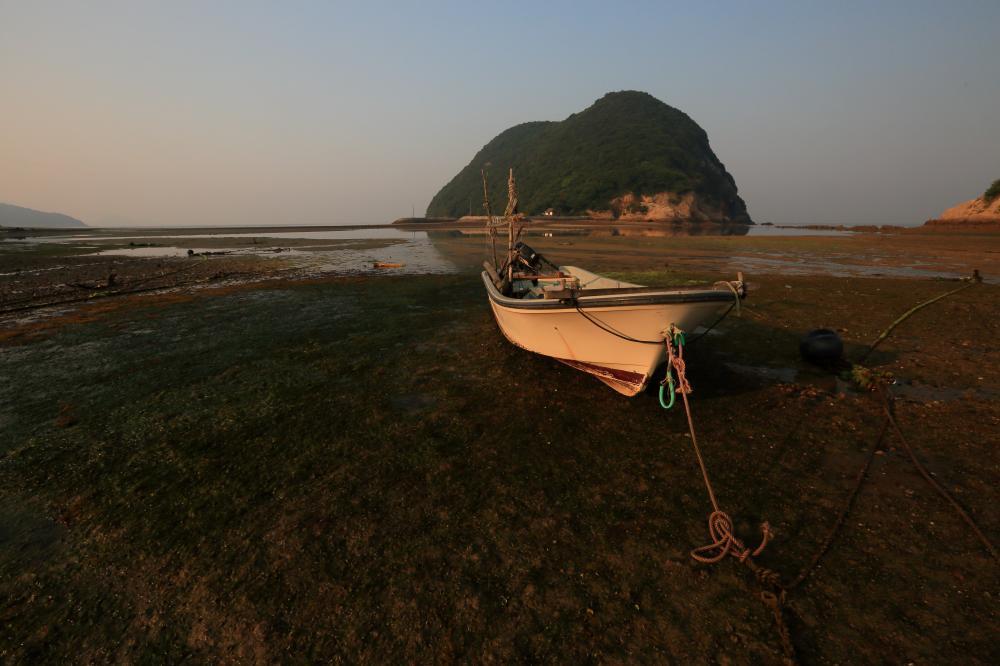 朝陽の中の小舟